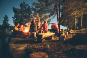 people sitting around a campfire in the woods